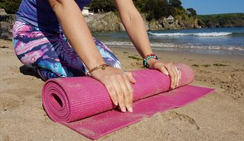 Yoga Mat being unrolled on Hope Cove Beach, near Kingsbridge
