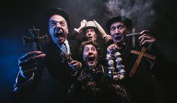 Dracula: The Bloody Truth by Le Navet Bete. Four performers stare at the camera holding garlic, crucifixes and a stake, all looking terrified.